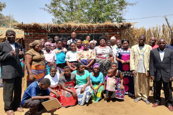 Health group members stand outside their garden, where they are farming food for the community.