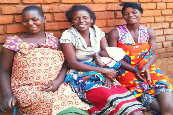 Three happy mothers posing outside their community group meeting with a brand new member!