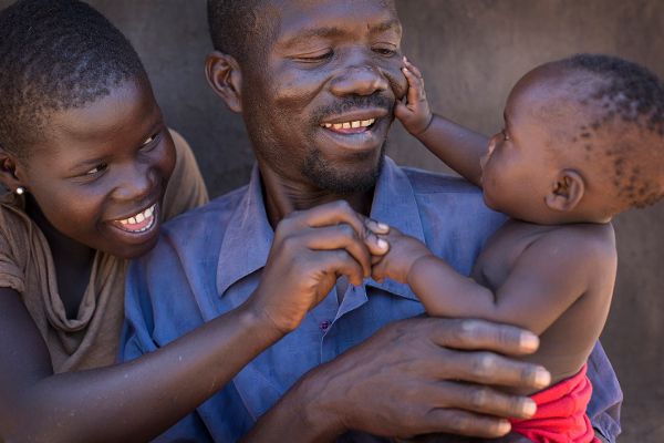 Innocent and George, Nancy's mother and grandfather, play and talk with baby Nancy. They've been supported by their women's health group.