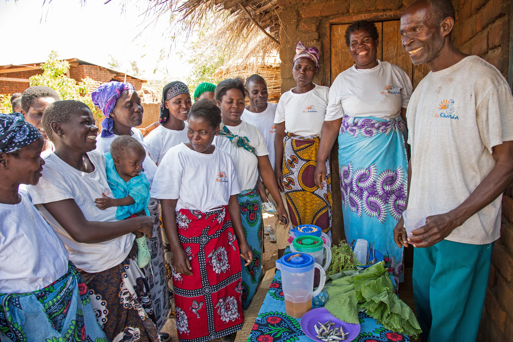 Joseph Saopa, the group leader, leading a cookery demonstration, with his students watching
