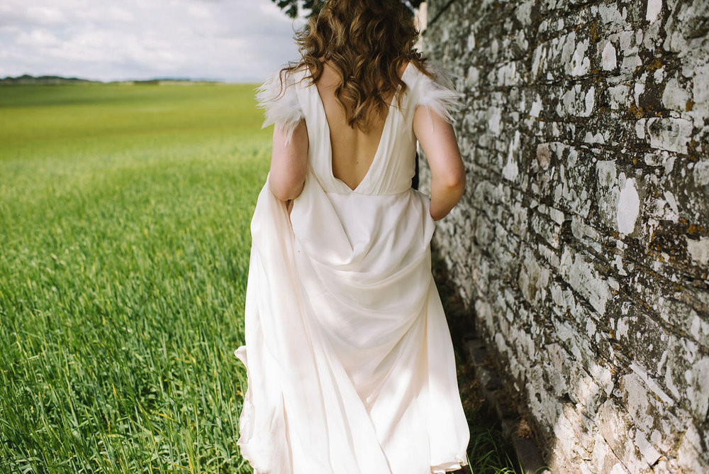 """Saskia - """"I wanted a dress that was elegant but effortless, and with a small detail which would make it stand out. The classic style of my dress, combined with the interesting details of the low cut V back and the feathered sleeves, was exactly what I was looking for."""""""
