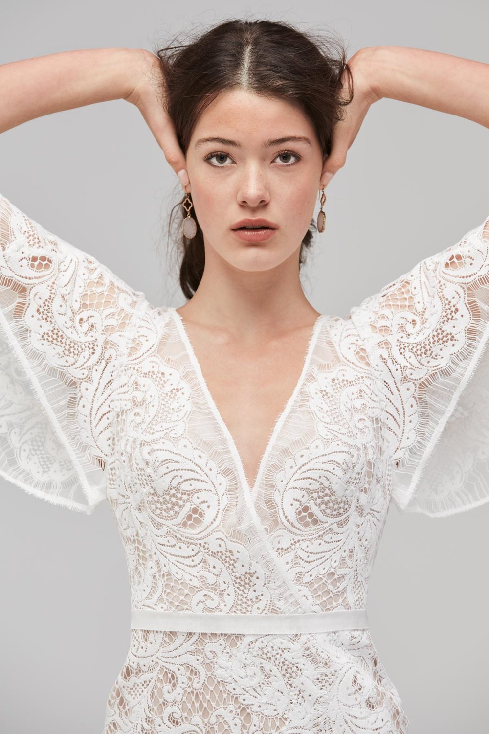 / 10 - WILLOWBY | UDARAFluttery winged sleeves of Moraea lace give Udara a fanciful feel. This romantic sheath features faux wrap styling with an open keyhole back and high side split.