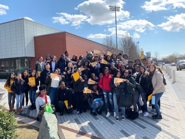 Students pose in front of Adelphi's mascot.   Photo Credit: Ms. Karen Giordano