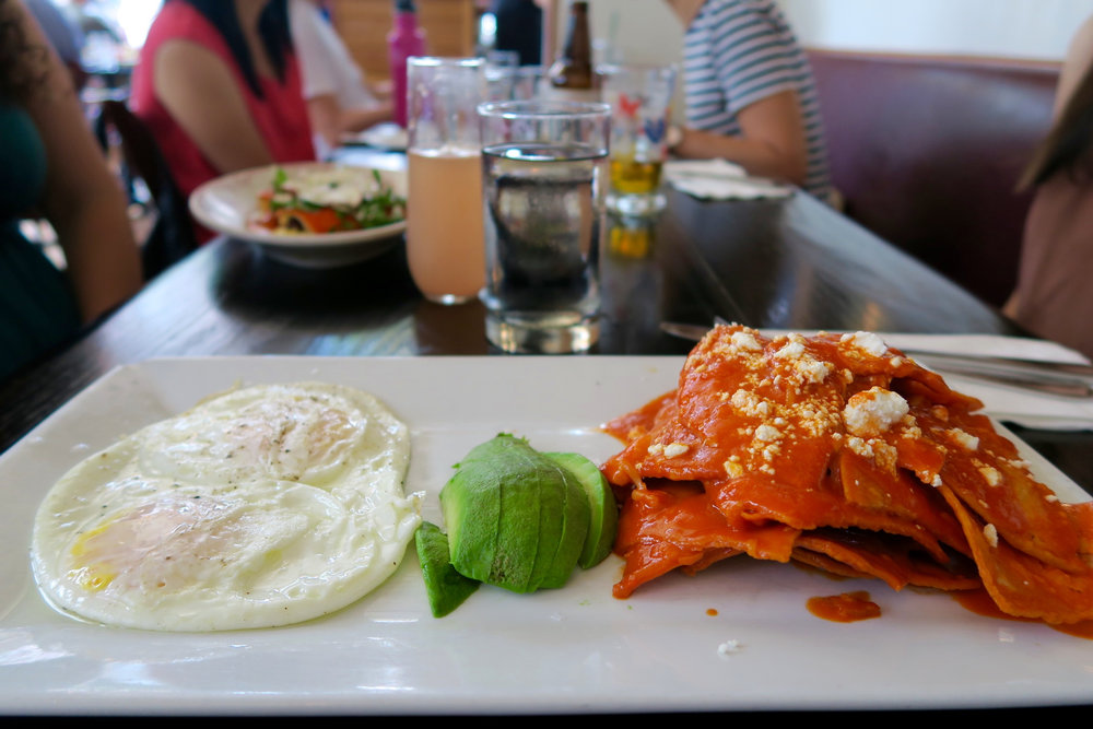 Chilaquiles: eggs over easy, spicy tortillas, and avocado