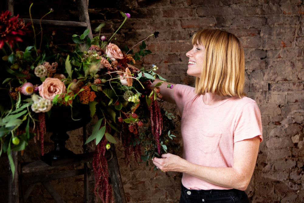 Vintage Florals  owner and lead designer Melissa Broadwell places the largest blooms and fills the gaps in her fall-dinner arrangement.