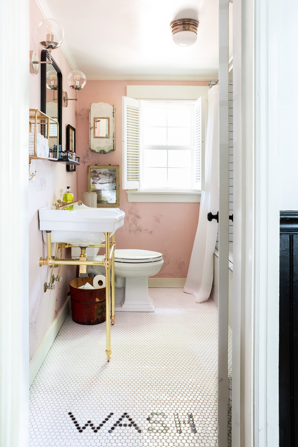 """No Southern home is complete without a stylish bathroom,"" Holly says of her brassy, gold-on-pink design for the cottage's renovated water closet. ""There's absolutely got to be a soaking tub, too."""