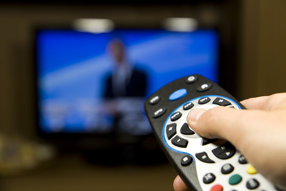 A remote control pointing to a blurry television.