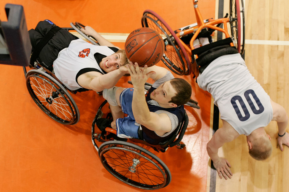 "Brandon Wagner, left, tries to intercept Drew Dokos' shot while Matt Buchi tries to lift himself up. ""The smallest guy on the court can keep the biggest, fastest guy out of the court just by having good chair position,"" head coach Mike Frogley said. ""A pick and roll in wheelchair basketball is the most deadly way to score."""