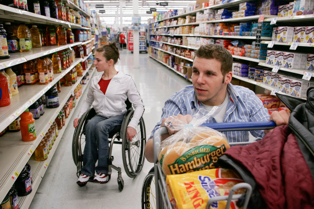 "Denny Muha and Amanda McGrory shop for food at Wal-Mart. Because Denny and Amanda are both in wheelchairs, ""it's easier to deal with any disability-related issues,"" Muha said. ""I think it's easier because there's less to explain."""