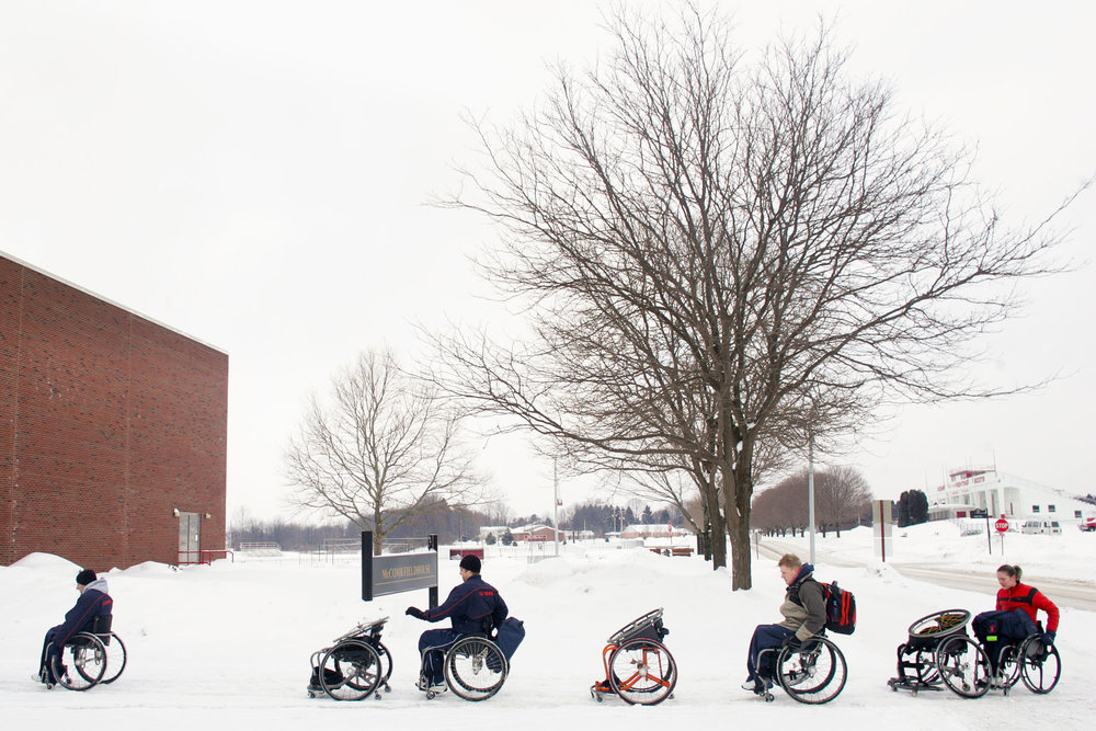 From left, Paul Ward, Brandon Wagner, Matt Buchi, and Edina Mueller push their game chairs through the snow on their way to a tournament at Edinboro University. Each athlete typically carries two chairs and spare wheels with them to every tournament. They don't have much traction with the uneven, snowy surface.