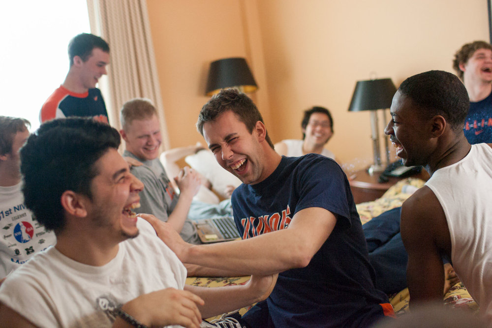 "From left, in front, Jaime Baltazar, Aaron Pike, and Brian Bell laugh together with teammates during a team meeting at their hotel. ""Off the court, they really interact with each other really well,"" head coach Mike Frogley said. ""And that's good — in the long run, that'll help them on the court."""