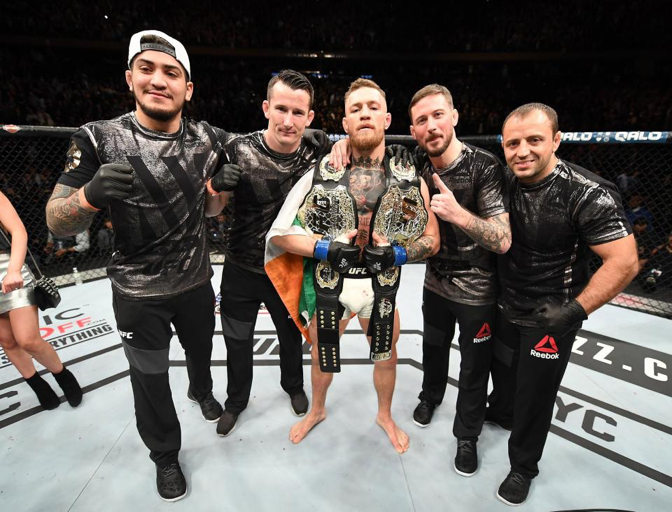 Conor McGregor posing with his team after winning the belt