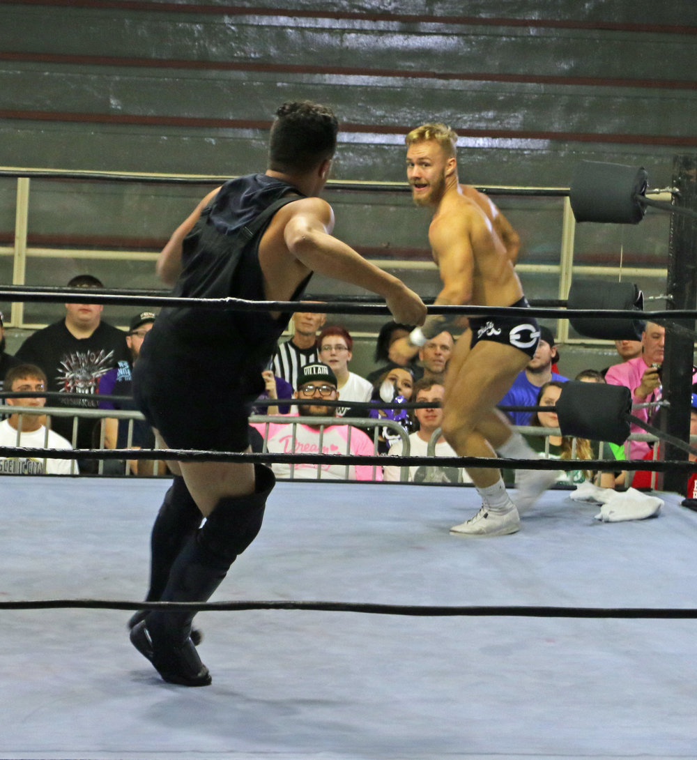 Tyler Bate, right, gets ready to charge TK Cooper.
