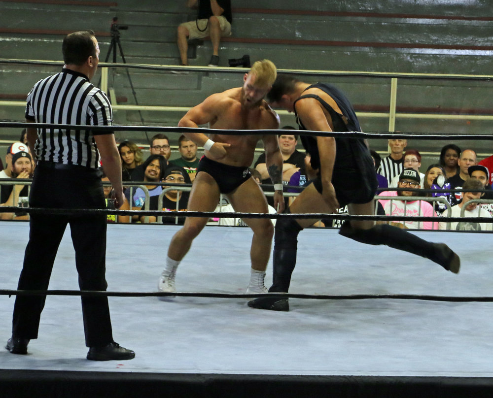TK Cooper, right, delivers a head-butt to Tyler Bate.