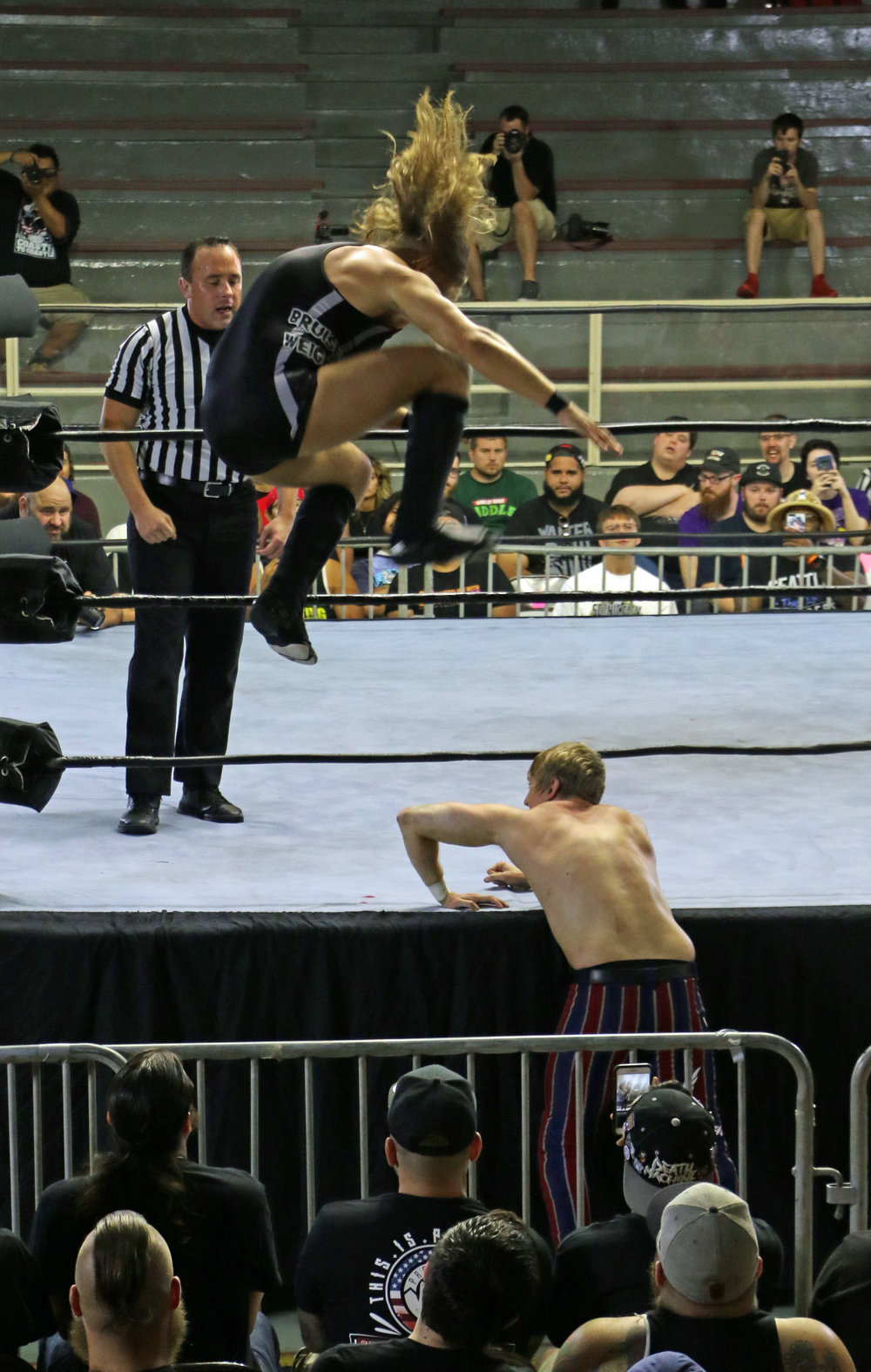 Pete Dunne goes to stomp the arm of Flash Morgan Webster on the ring apron.