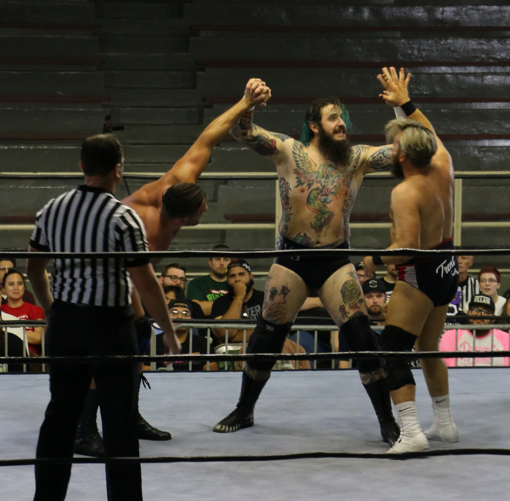 Brody King, center, puts dual knucklelocks on Elliot Sexton, left, and Trent Seven.