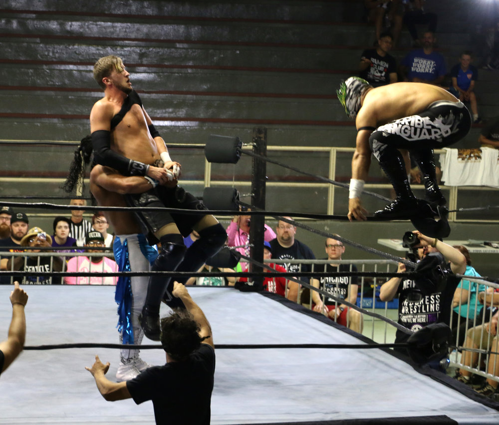 Flamita, right, prepares to throw a dropkick off the top rope as his partner Bandido holds up Chris Brookes.