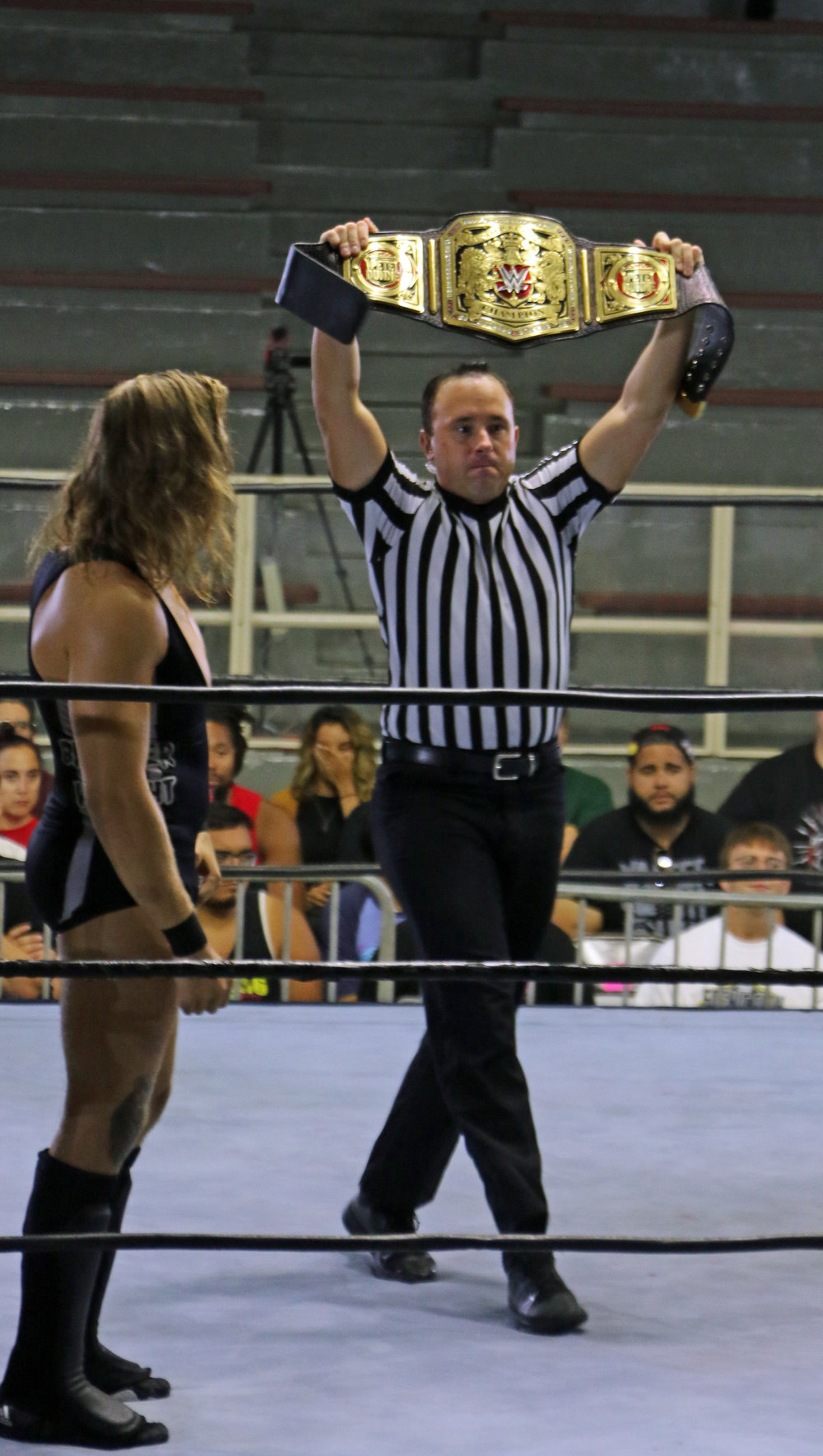 Pete Dunne, left, watches, as the referee holds up the WWE United Kingdom Championship before the bout against Flash Morgan Webster.