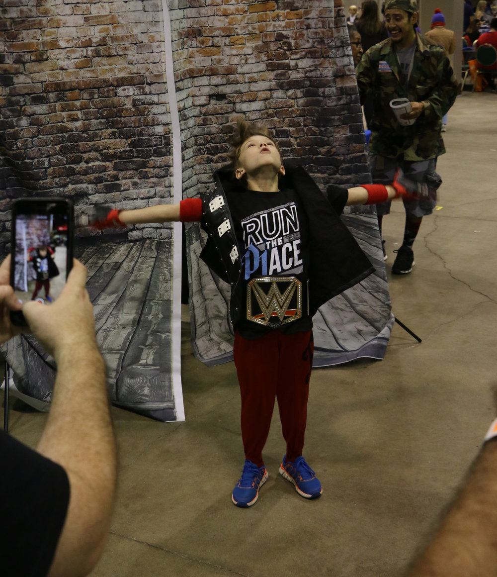 A young boy dressed up as AJ Styles poses during his entrance at the Too Sweet Cosplay booth.