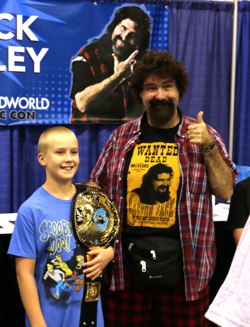 WWE Hall of Famer Mick Foley, right, poses for a picture with a young fan at Wizard World Chicago on Friday, August 24, 2018.  (Photo by Mike Pankow)