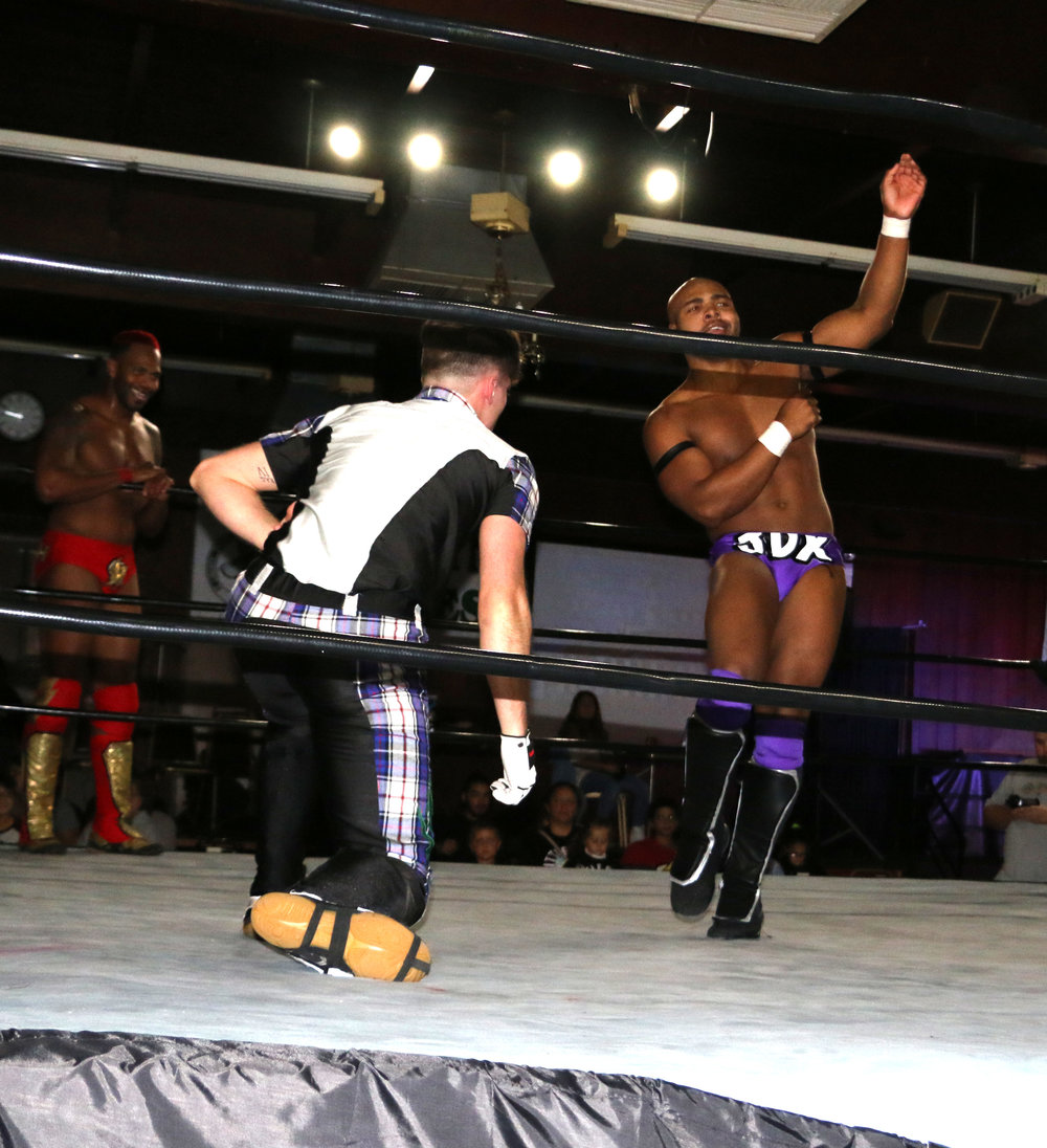 "JDX, right, taunts Dale Springs with Springs' own ""golf swing"" taunt during the eight-man tag team match."