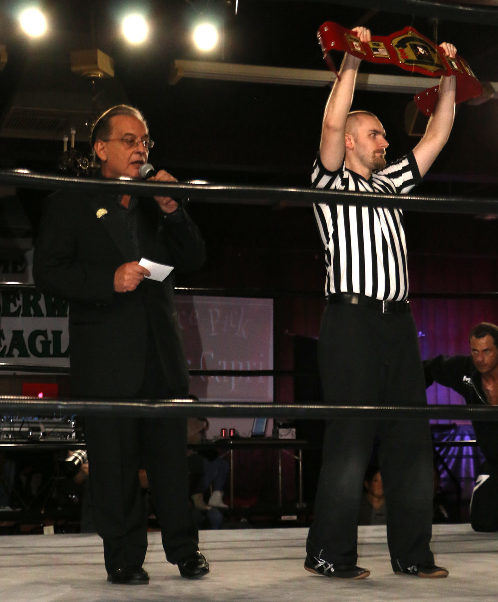 Gary Michael Cappetta introduces the BCW Championship match as the referee holds up the title belt.