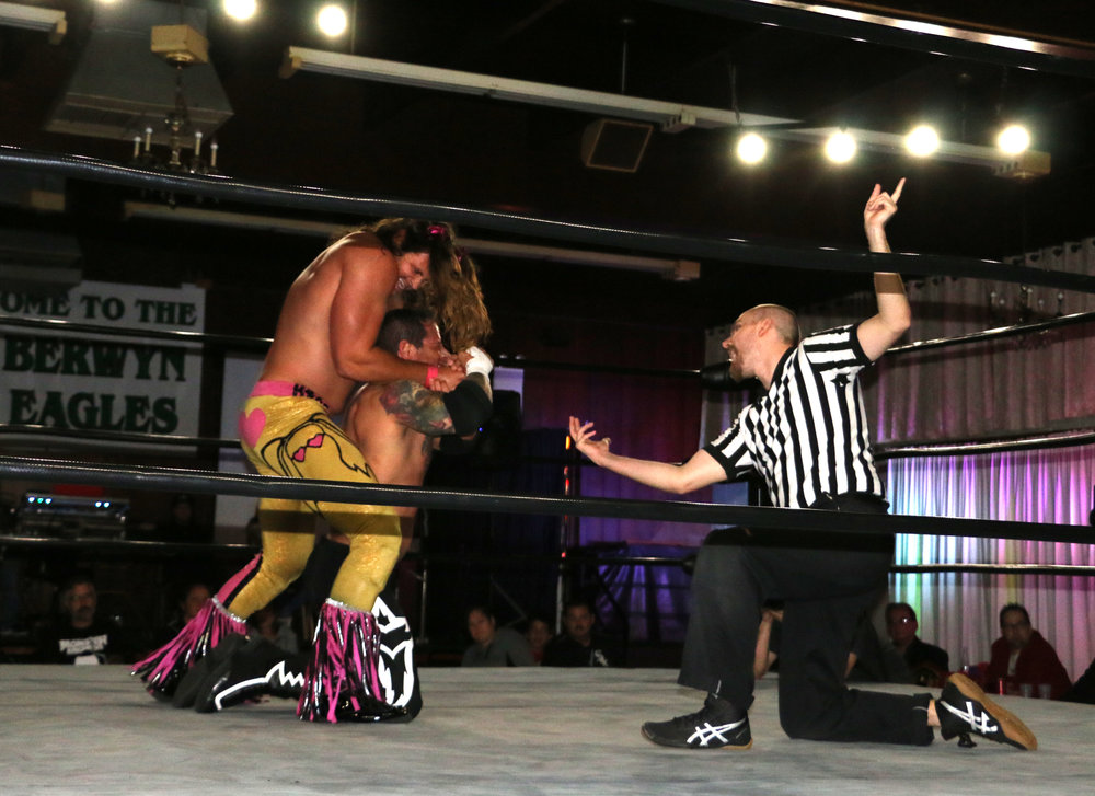 The referee checks in on Vic Capri as Jaden Roller tightens his grip during the BCW Championship match.