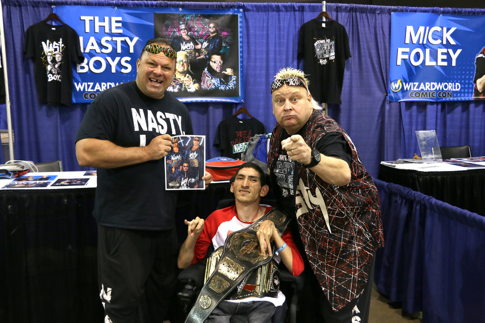 Wrestling fan Niko Melendez, center, poses with Jerry Sags, left, and Brian Knobbs, right, during the Nasty Boys' appearance at Wizard World Chicago on Friday, August 24, 2018.