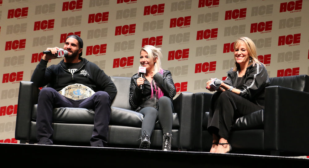 Seth Rollins, left, answers a fan question during the WWE panel as Alexa Bliss, center, and Lilian Garcia look on.