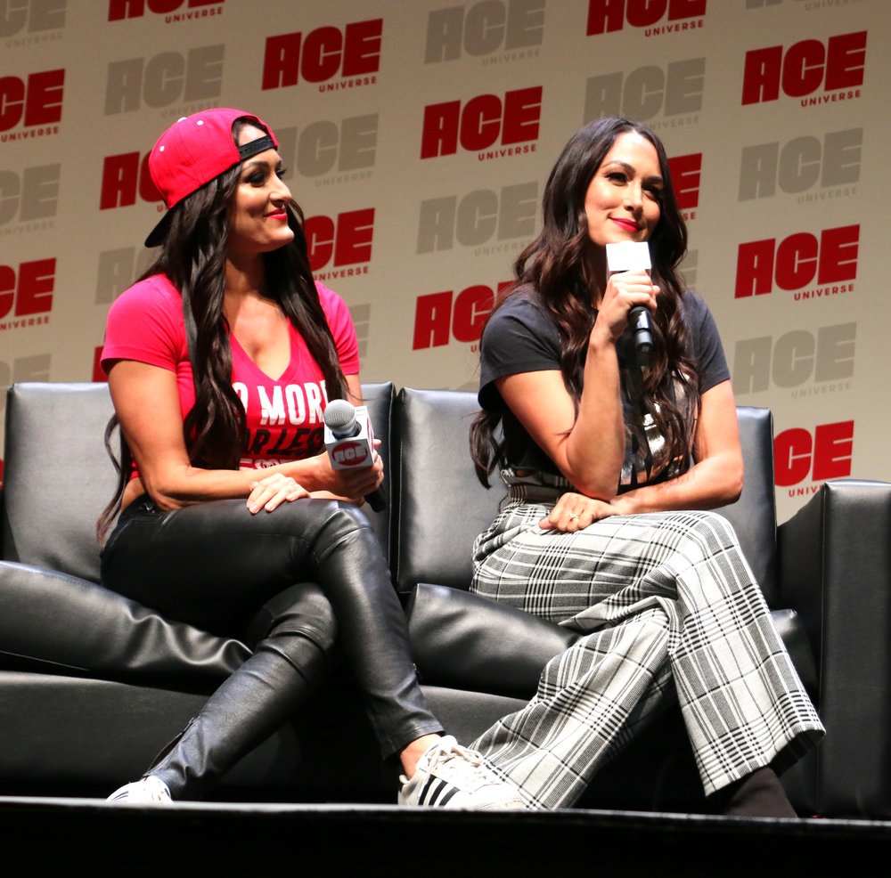 Brie Bella, right, answers a question, while Nikki looks on.