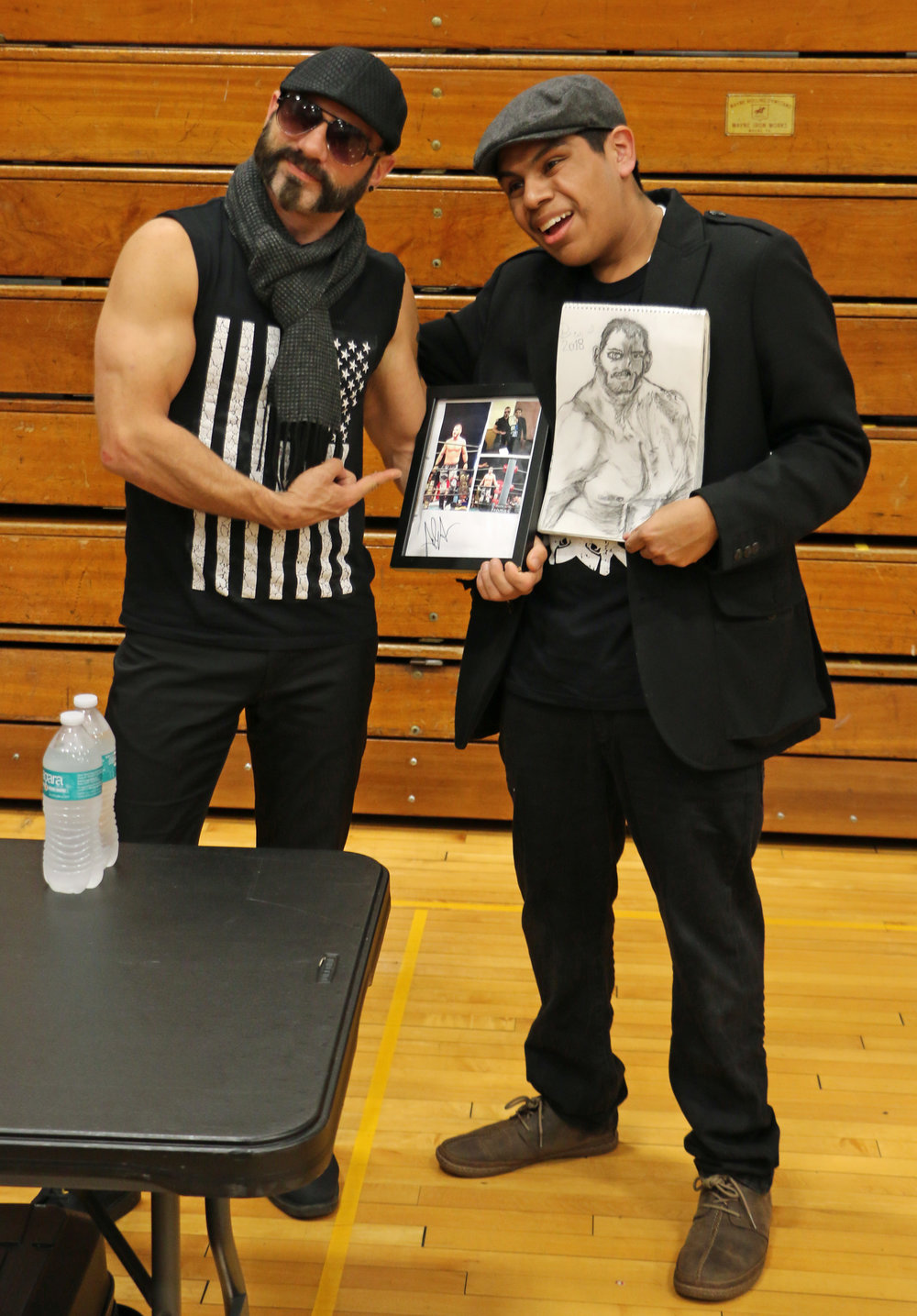 Austin Aries poses with a fan and his artwork at the VIP Fan Fest.