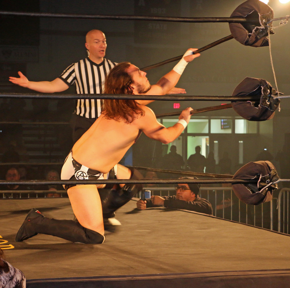 Andrew Everett struggles to get to his feet as referee Brian Stiffler looks on.