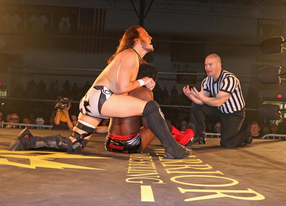 Andrew Everett controls Rich Swann as referee Brian Stiffler checks on Swann.
