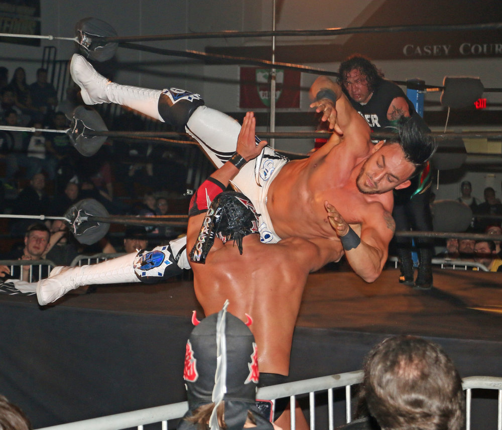 Daga dives onto Dragon Lee at ringside.