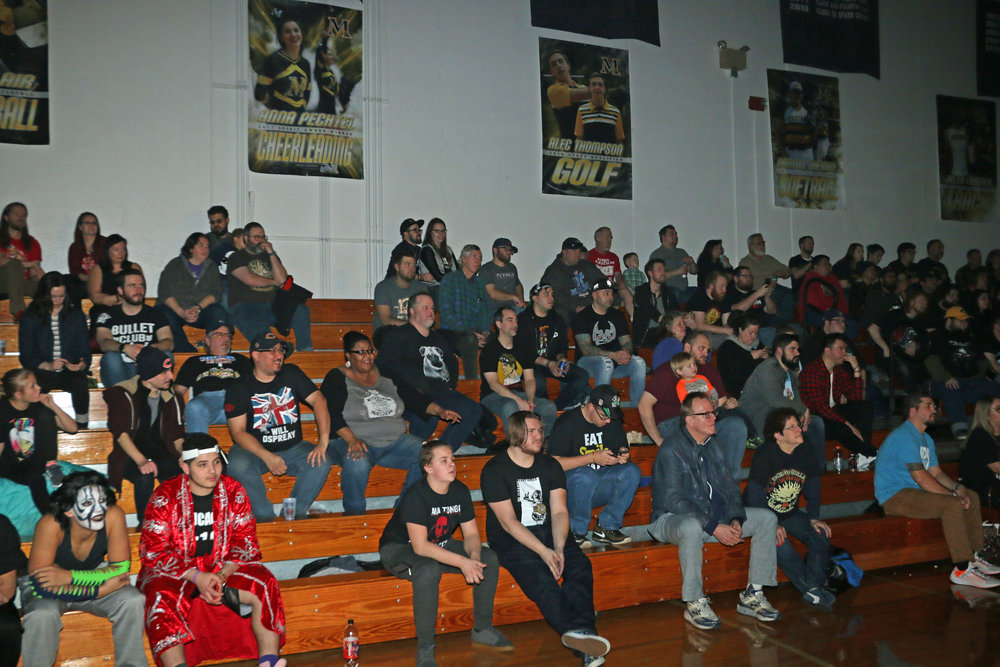 The crowd is engaged in the Lucha Libre trios match.