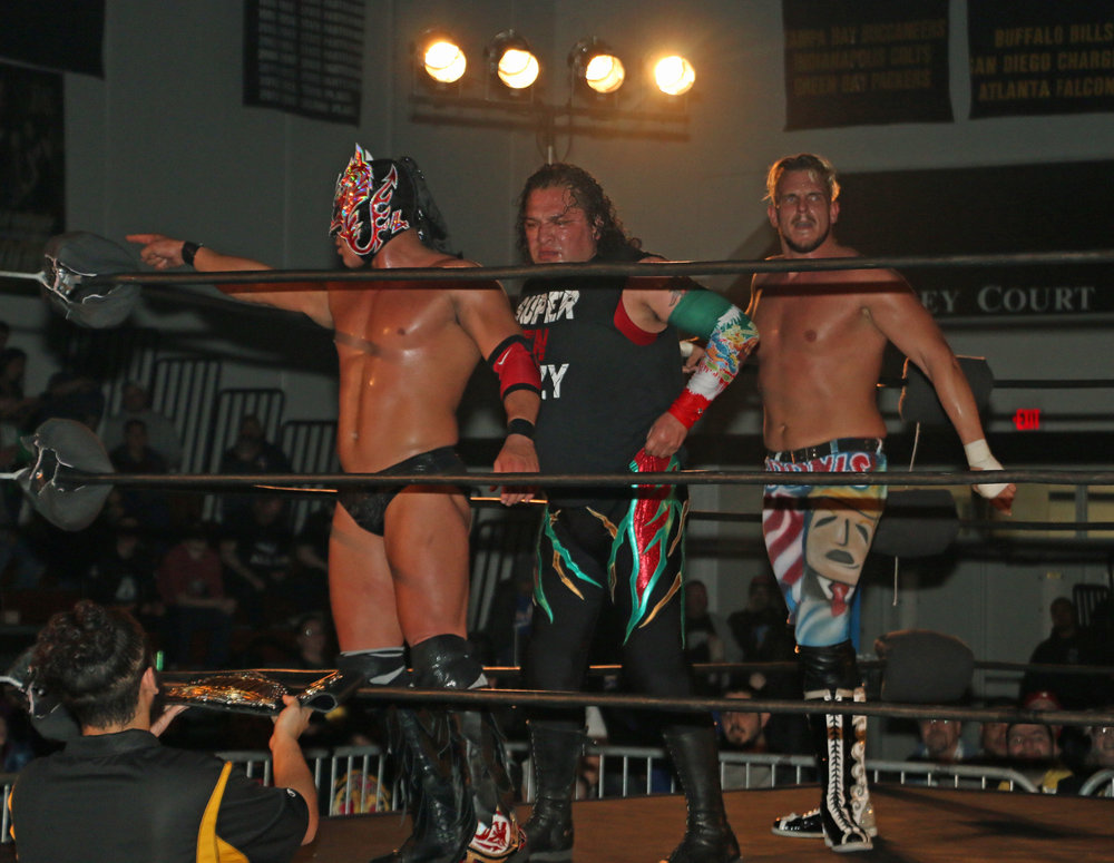 The team of Dragon Lee, Super Crazy and Sam Adonis celebrate victory in the Lucha Libre trios match.