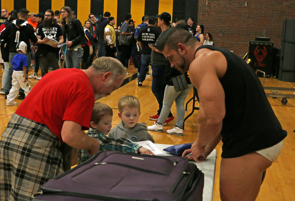Warrior Wrestling Champion Brian Cage signs an autograph for kids during the intermission meet and greet.