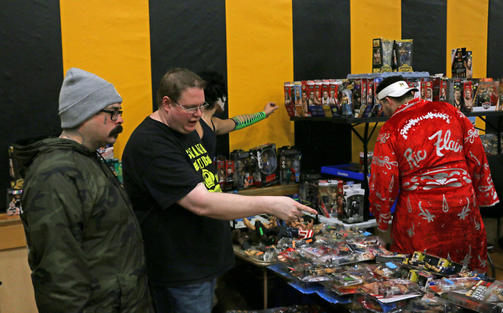 Toy dealer Bryan Koltz, center, hawks some of his wrestling action figures at the fan fest during intermission.