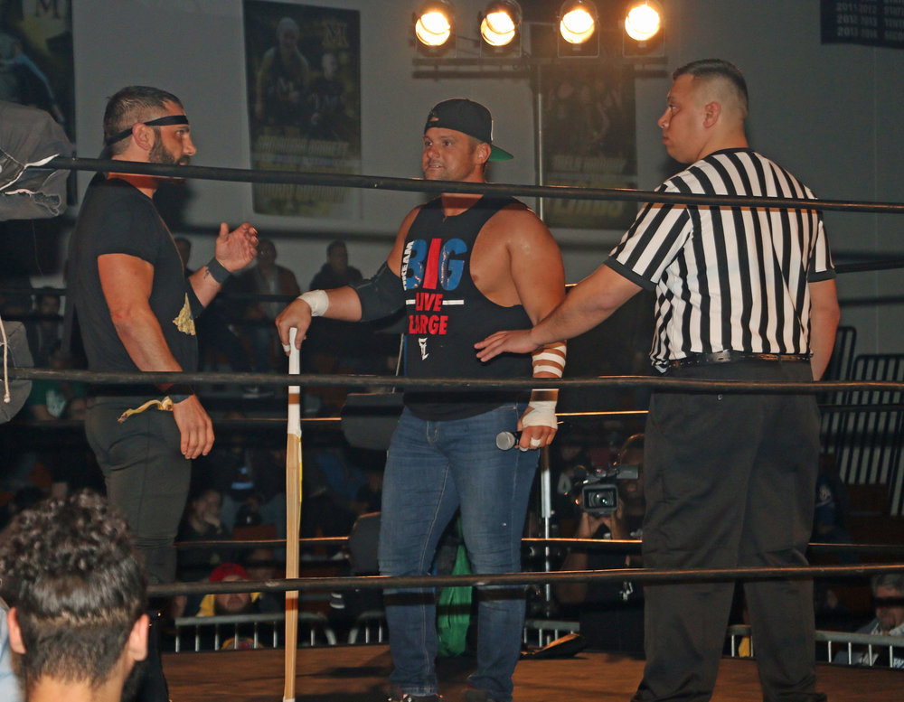 Austin Aries, left, and Eddie Edwards stare each other down as referee Jeremy Tillema looks on.
