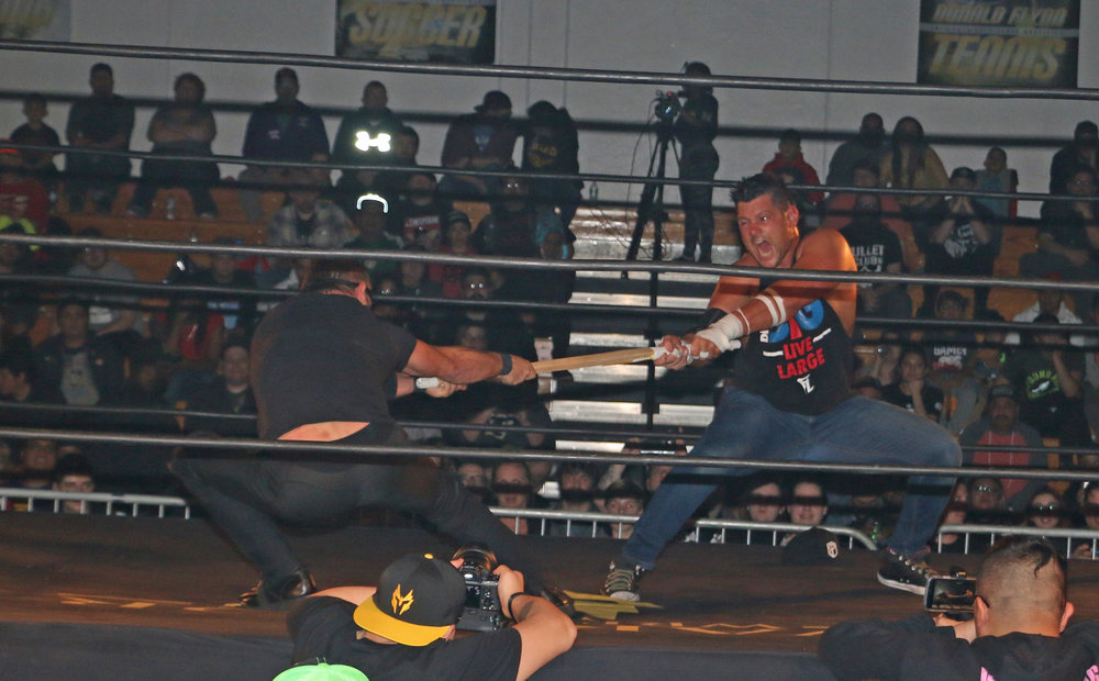 Eddie Edwards, right, tries to pull the kendo stick away from Austin Aries.