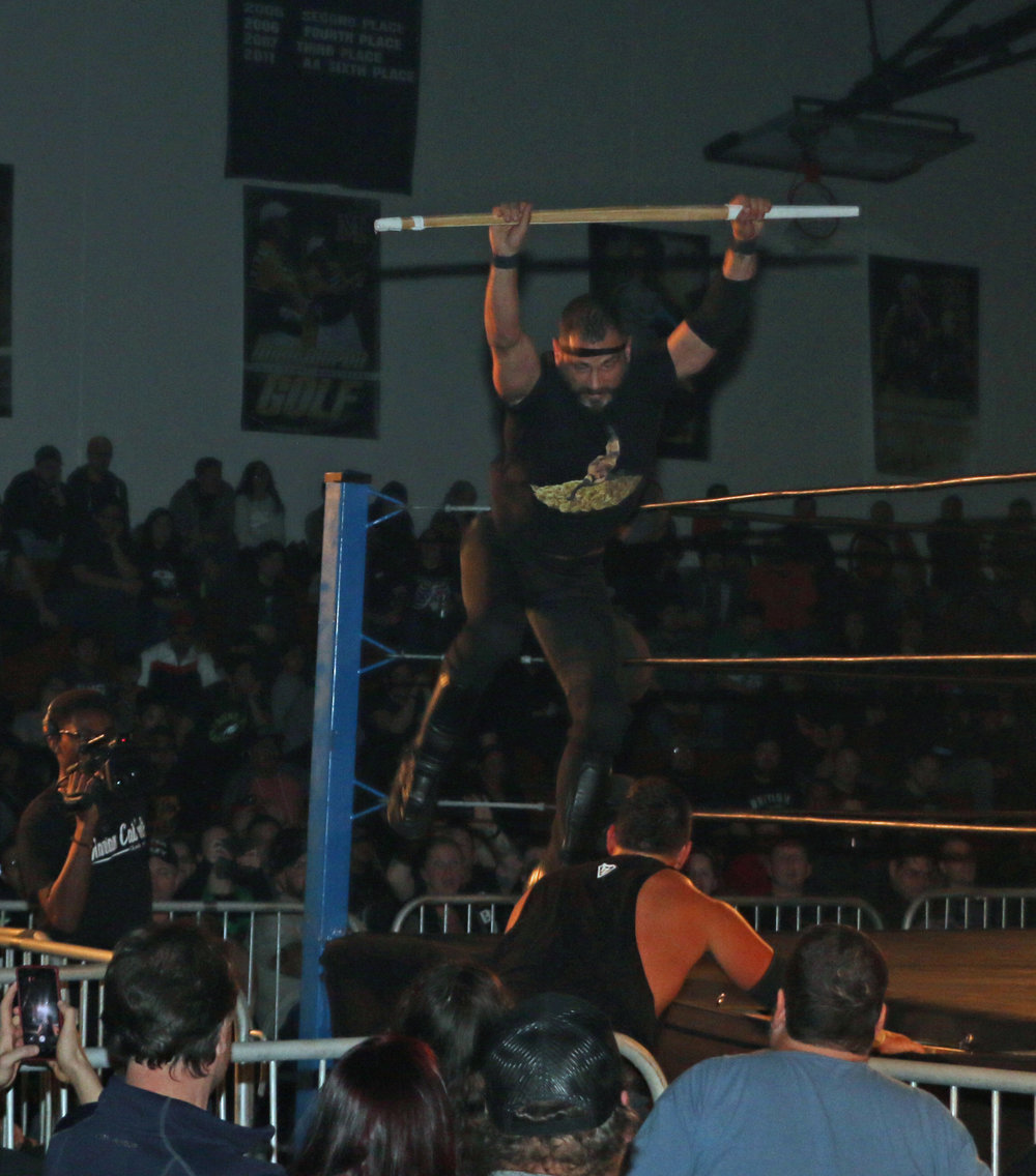 Austin Aries jumps off the top rope with the kendo stick in an effort to attack Eddie Edwards.