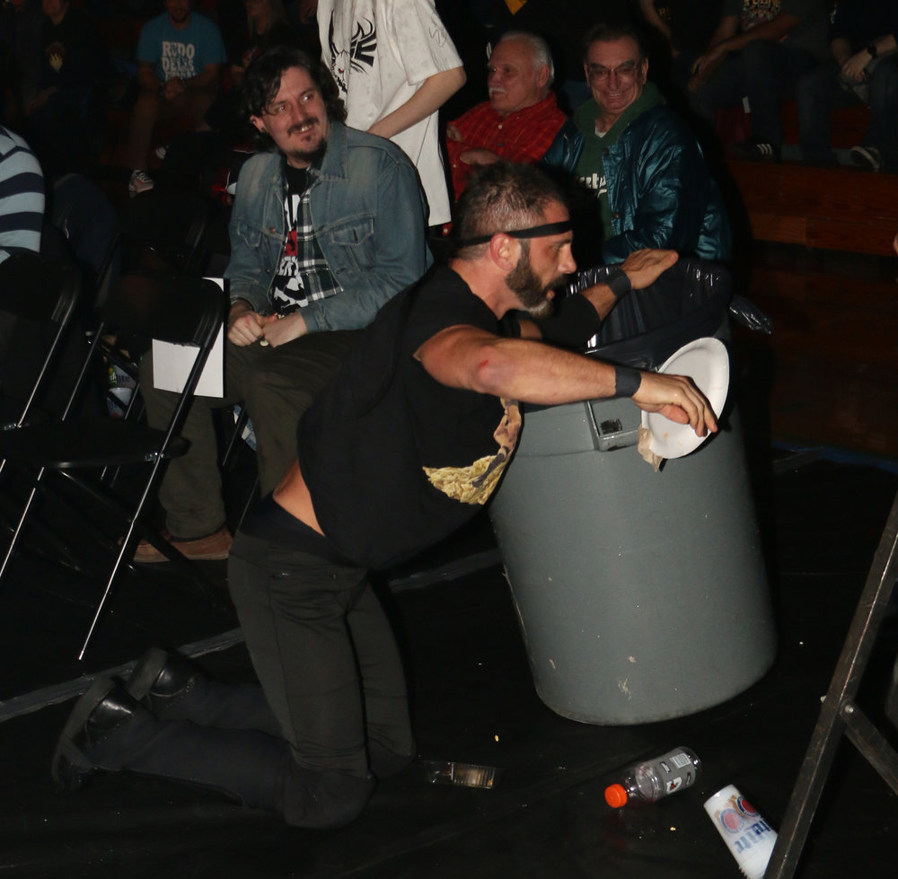 Austin Aries stumbles into a garbage can around ringside during his brawl against Eddie Edwards.