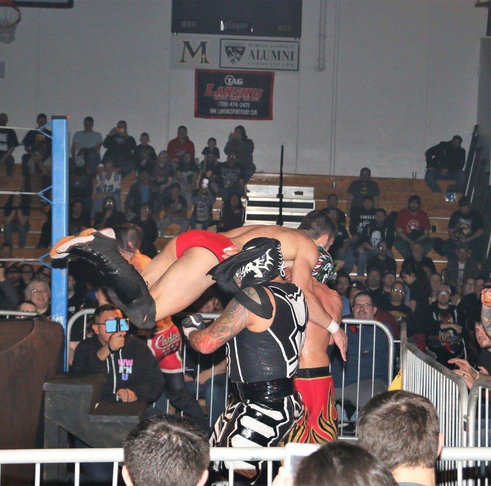 The Lucha Bros. rebuff a suicide dive by A-Kid.