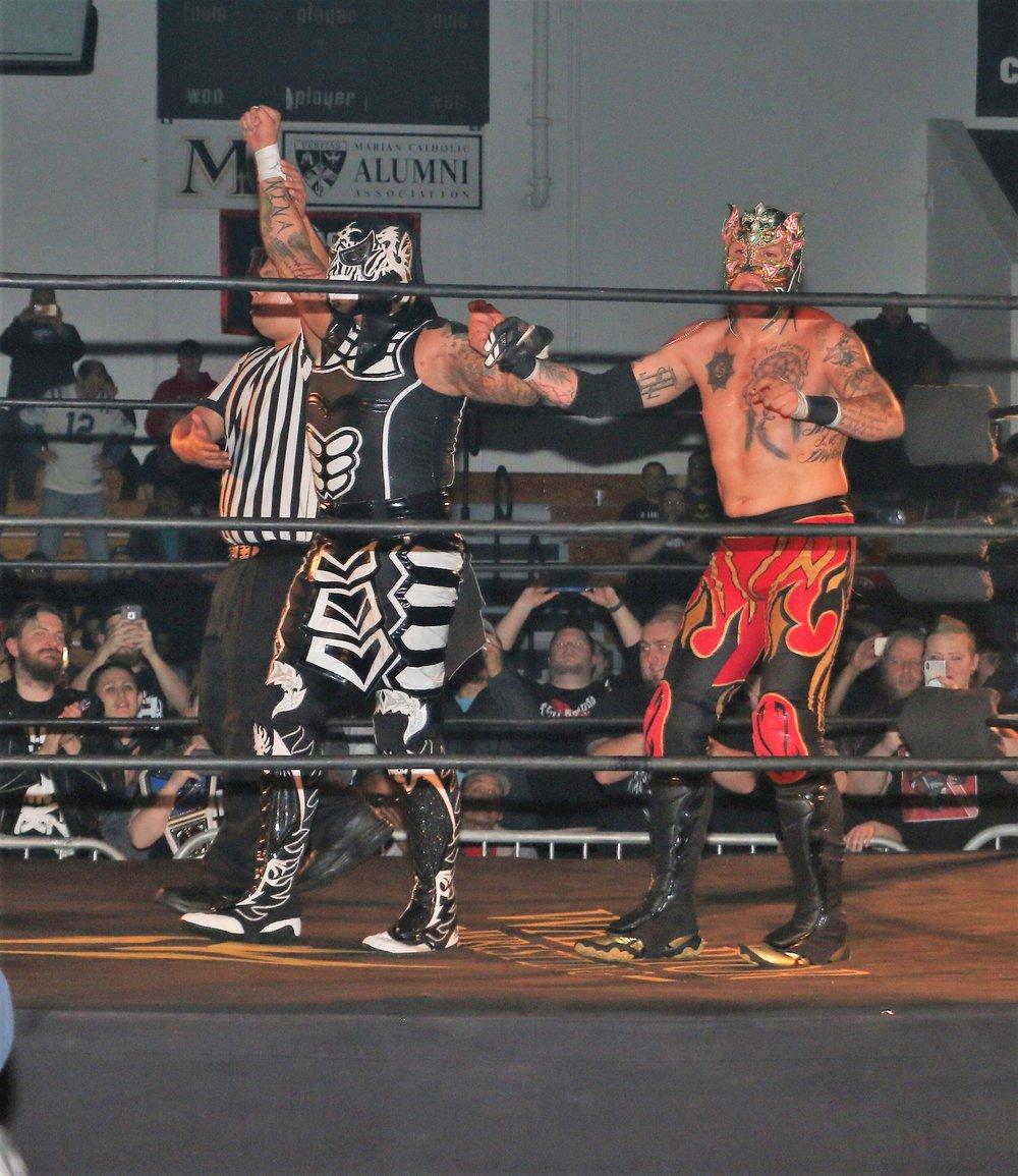 Penta El 0M, left, and Fenix celebrate their tag team victory.