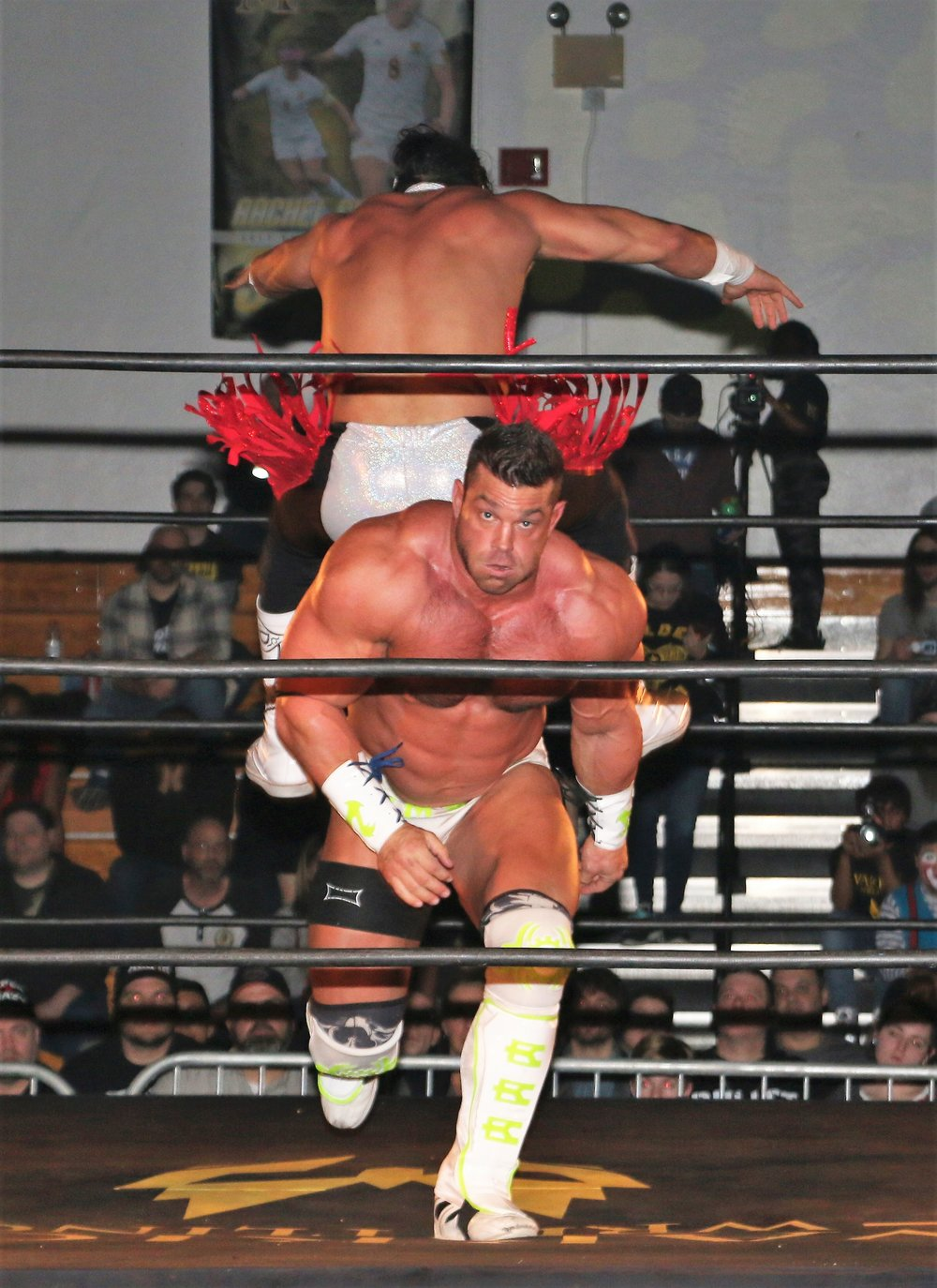Brian Cage runs toward the ropes after Bandido performs a leapfrog.