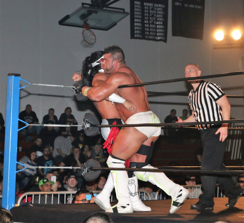 Brian Cage delivers a clothesline on Bandido in the corner.