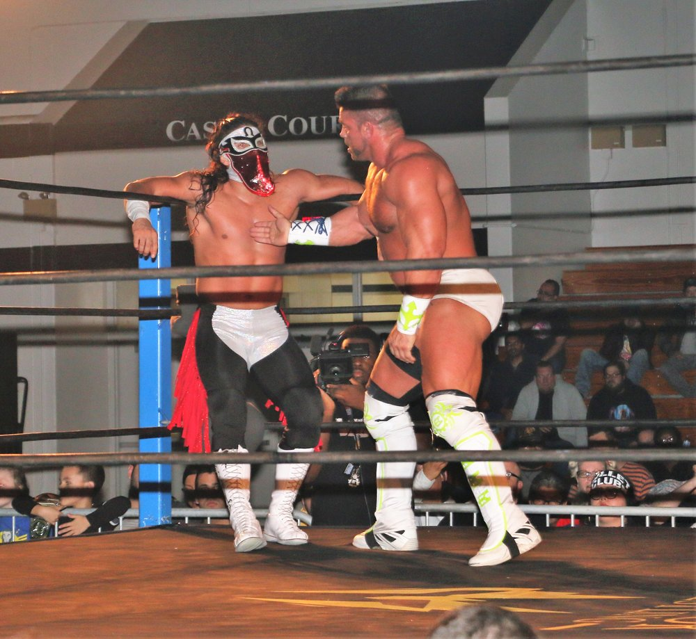 Warrior Wrestling Champion Brian Cage prepares to throw a knife-edge chop on Bandido in the corner.