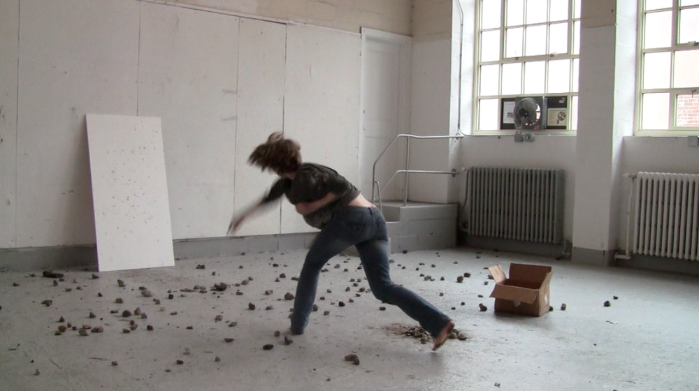 The Stones We Carry   Still image from the performance  Panel, rocks, cardboard box  2014