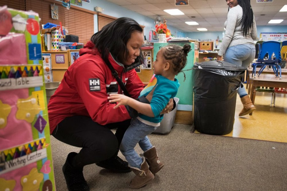 Getty/The Washington Post/Linda Davidson  Monique Burton picks up her daughter from a children's day care center in Greenbelt, Maryland. At the time, Burton was working toward her associate degree, December 2016.