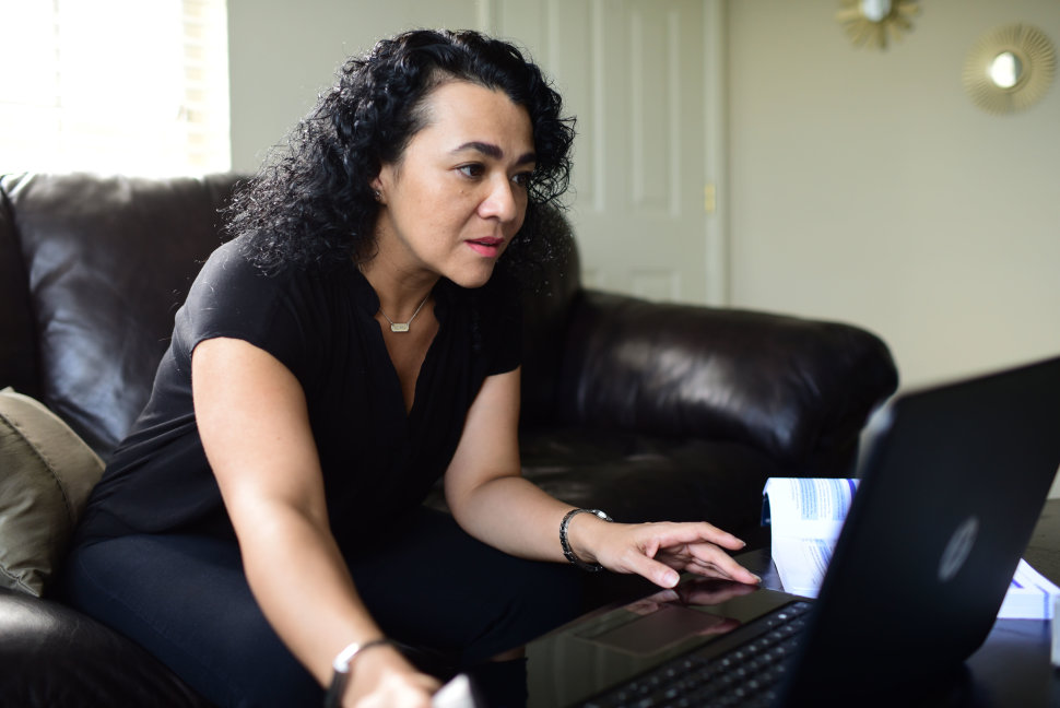 CHERYL GERBER  University of New Orleans senior Silvia Gomez, 42, looks over homework at her Metairie, La., apartment. Gomez wakes up around 4 a.m. for the first of her two jobs, working 12 to 14 hours per day while attending classes and raising her daughter.